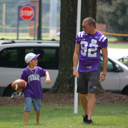football player walking with child